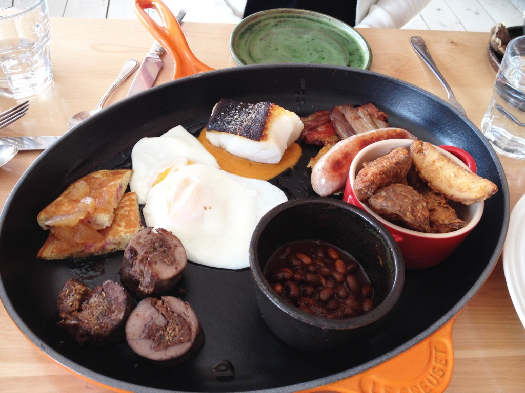 A large hot skillet of breakfast meats, cod, beans and pancakes.