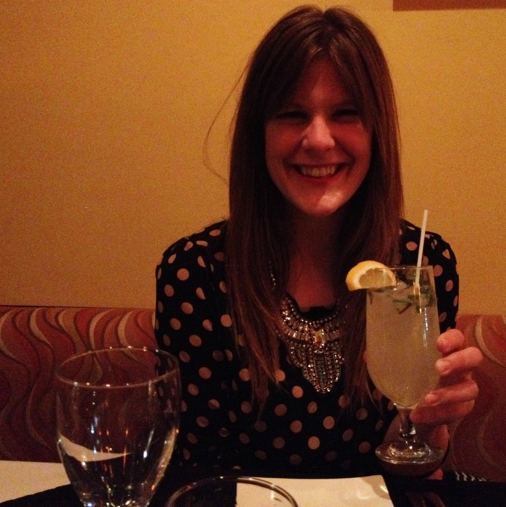 A young lady sitting in restaurant drinking a large cocktail.