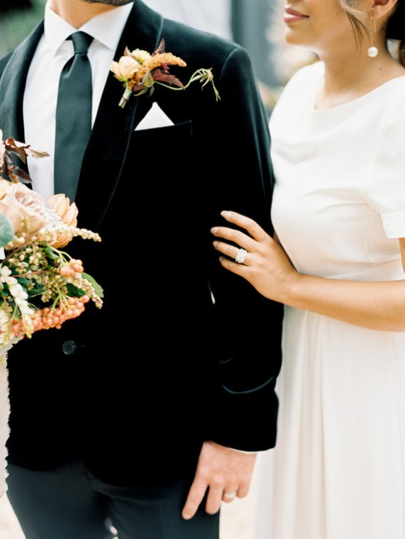 The groom wears a fitted velvet tux and the bride an elegant sleek gown to create elegant modern fall wedding style.