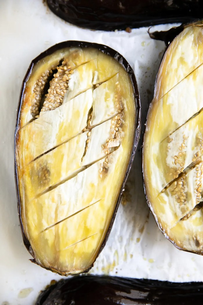 Roasted eggplant halves skin-side-up on a large baking sheet