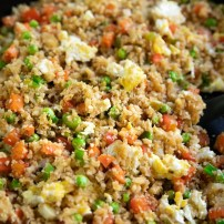 Cauliflower fried rice cooking in a black skillet.