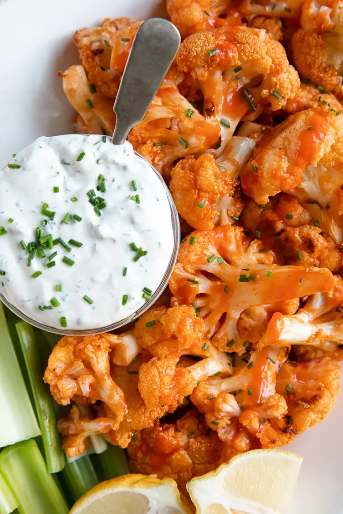 White plate with baked buffalo cauliflower and ranch dressing.