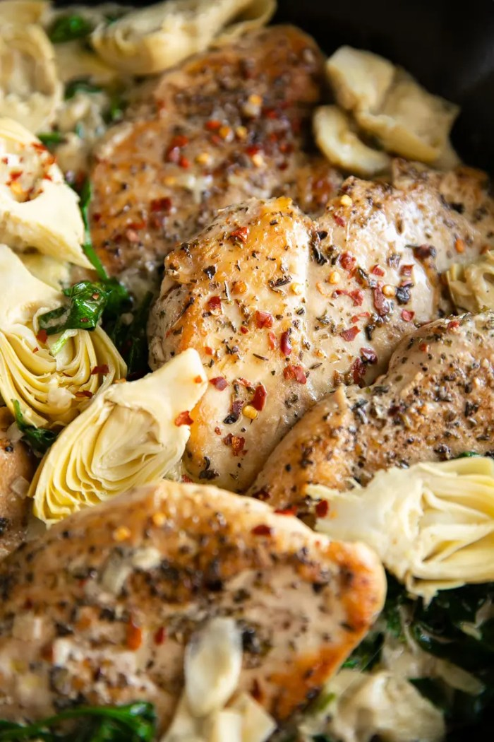 Chicken breasts surrounded by artichoke hearts in a cast iron skillet.