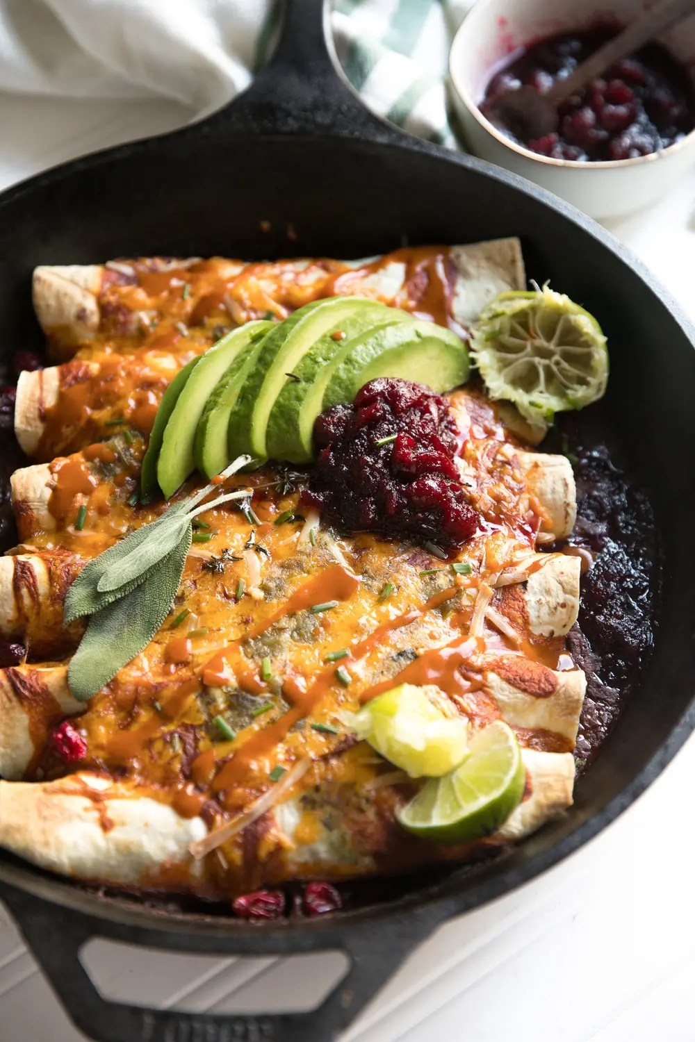 Leftover Thanksgiving Enchiladas filled with turkey, stuffing, leftover vegetable casserole, cheese, and cranberry sauce.