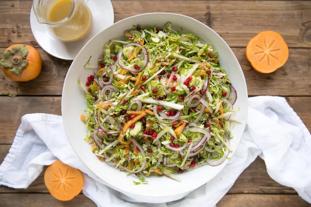 Shredded Brussels Sprout Persimmon Salad. Filled with some of falls finest like pomegranates, walnuts, pomegranates, apples, Brussels sprouts and drizzled with light dijon vinaigrette.
