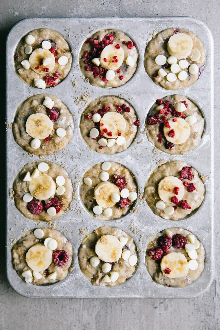 muffin tin filled with batter for banana coconut raspberry muffins with white chocolate chips