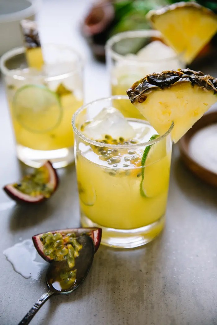 Glasses filled with ice, passion fruit, lime wedge, pineapple margarita