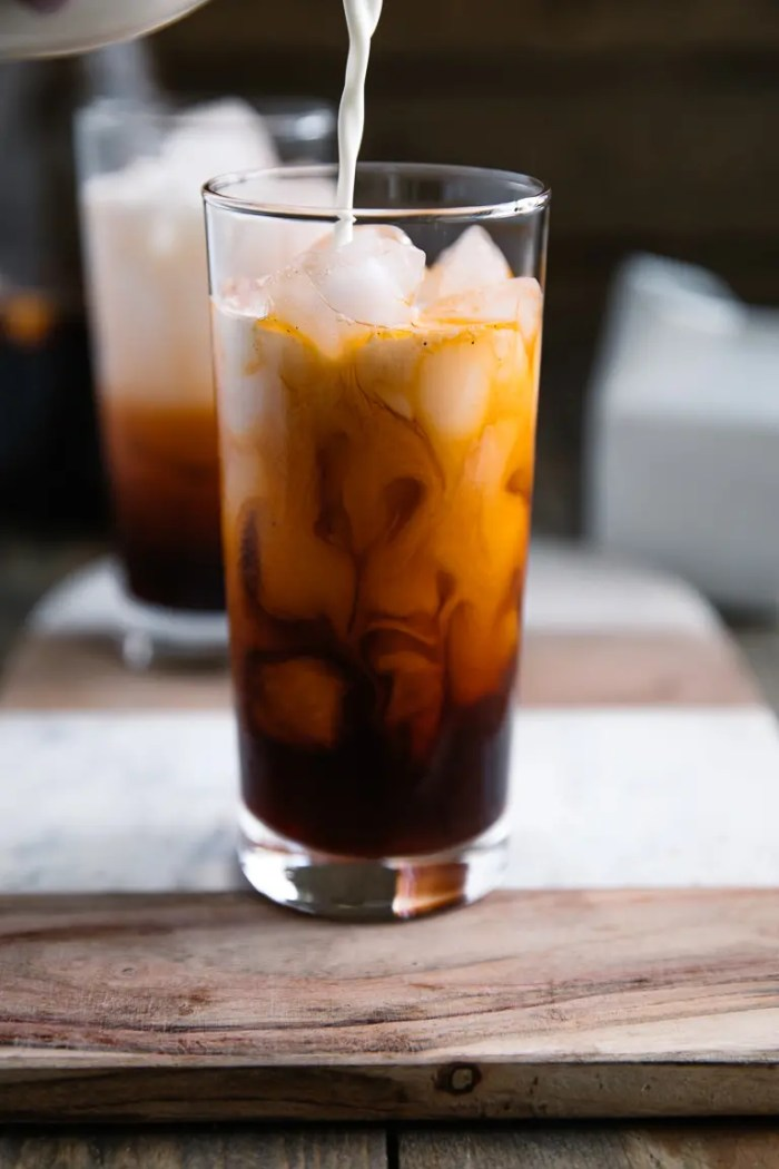 Pouring cream into glass filled with Thai Iced Tea