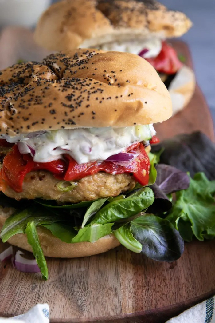 Prepared Grilled Turkey Burgers with fresh greens, roasted red peppers, and cucumber yogurt topping