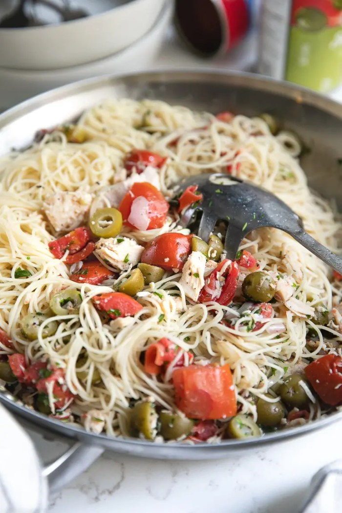 Side shot of Angel Hair Pasta with tomatoes, green olives, and chicken mixed together in a large skillet