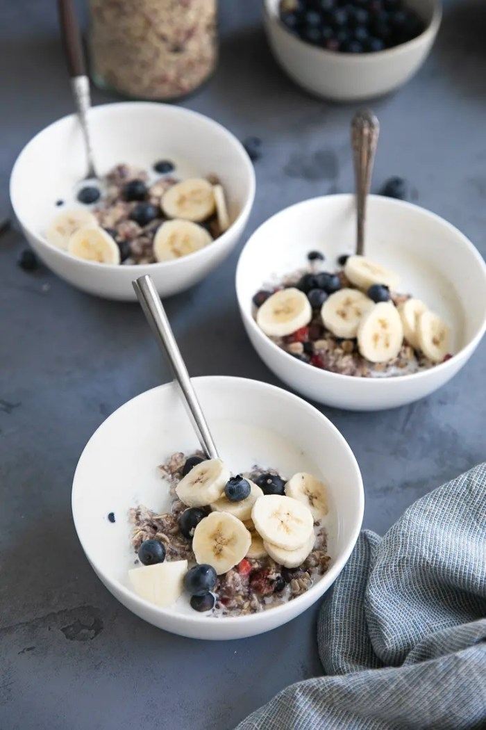 Three bowls of homemade berry oatmeal with banana and blueberries