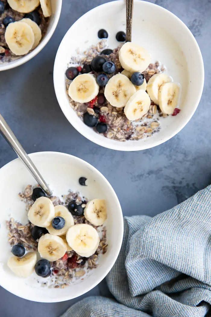 Two white bowls of Mixed Instant Berry Oatmeal filled with cold milk and topped with sliced banana.