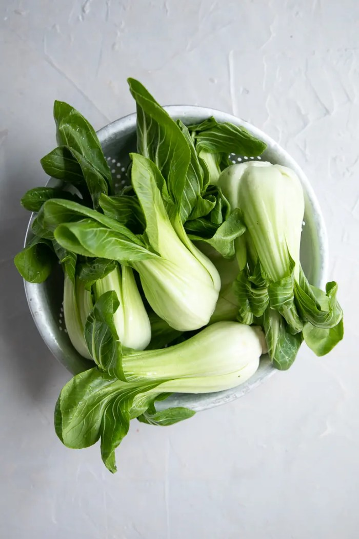 Raw baby bok choy in an old antique tin strainer.