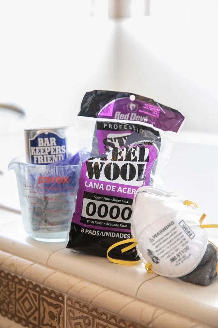 Supplies needed to clean glass shower doors- Bar Keepers Friends, gloves, 0000 Super Fine Steel Wool, and a mask.