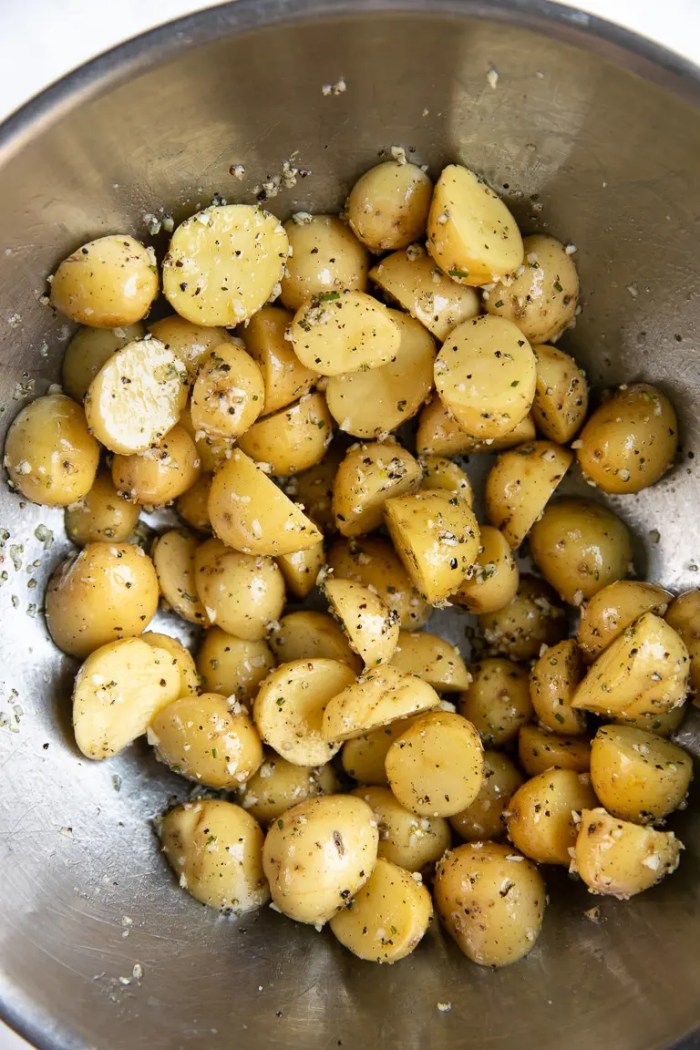 Large mixing bowl filled with baby potatoes covered in olive oil, garlic, salt, pepper, and minced rosemary.