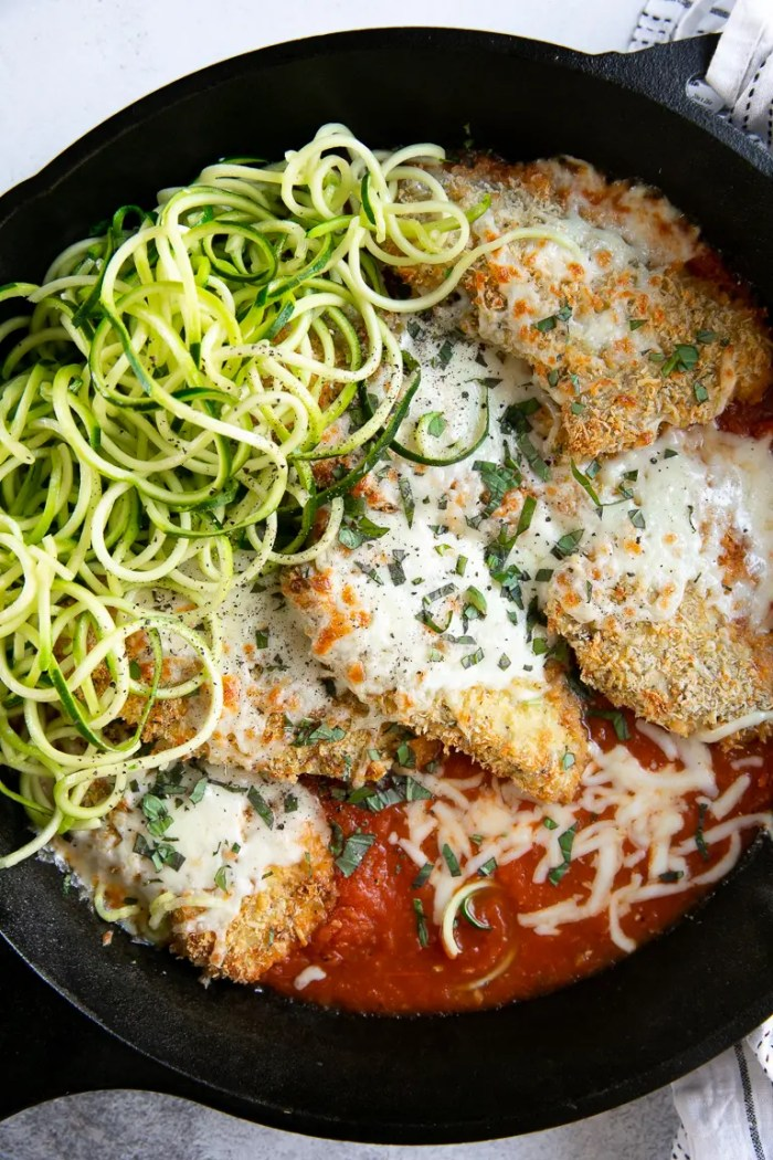 Baked chicken parmesan cutlets in a skillet with homemade marinara sauce, baked and covered with cheese.