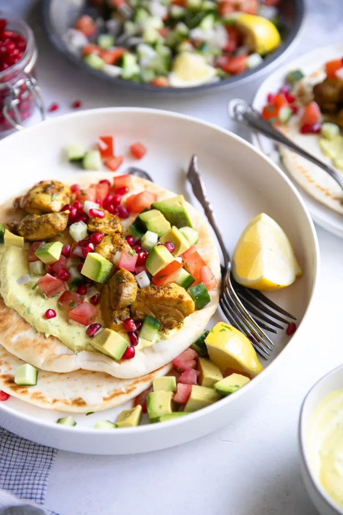 Tandoori chicken gyros with avocado pomegranate salsa on a while plate.