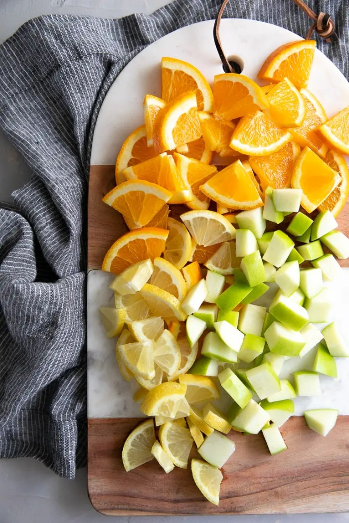 Cutting board with sliced oranges and lemons and chopped granny smith apples.