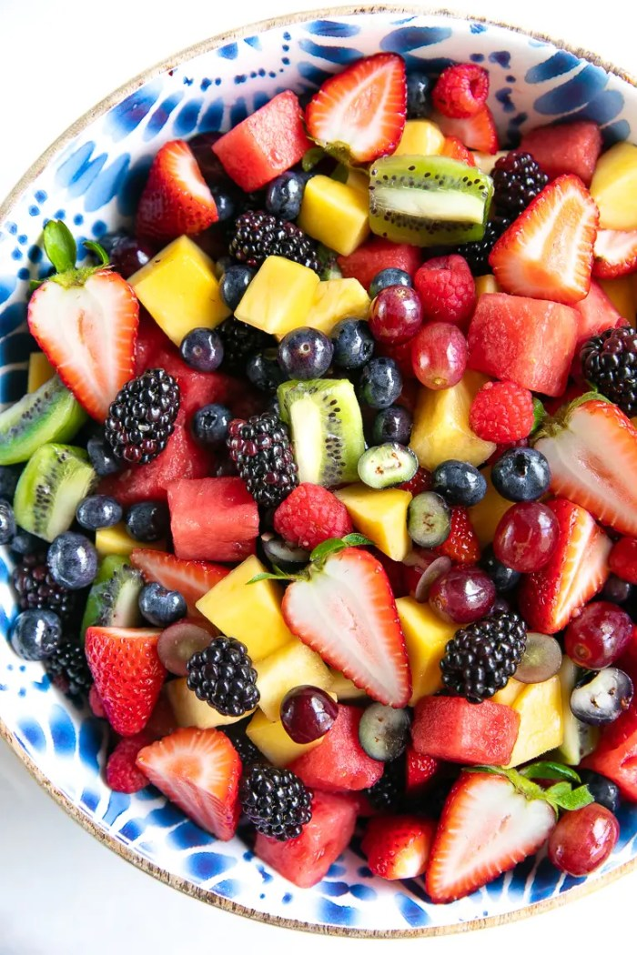 Large salad bowl filled with a variety of different fresh fruit including blackberries, ,strawberries, grapes, pineapple, kiwi, and watermelon.