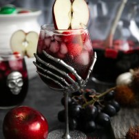 Large skeleton hand wine goblet filled with red sangria made with raspberries, blackberries, apples, and Sprite.
