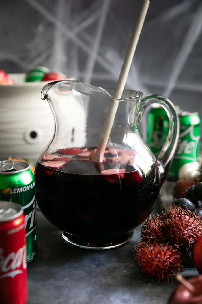 Large pitcher filled with Halloween Sangria made with raspberry liqueur, apple juice, pomegranate juice, vodka, and red wine.
