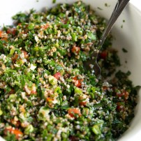 Large white serving bowl filled with bulgur tabbouleh salad.