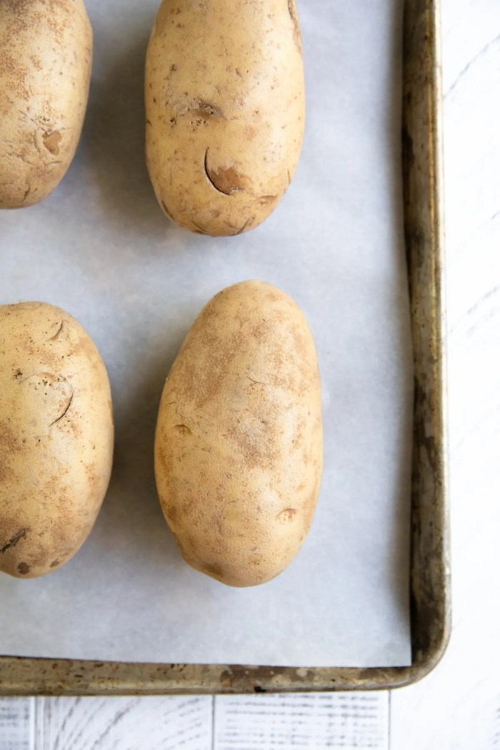 Unbaked washed russet potatoes on a baking sheet.