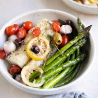 Two plated serving bowls with roasted asparagus and lemon baked cod topped with olives, cherry tomatoes, and fresh thyme.