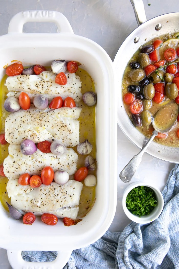 White baking dish filled with four cod fillets, cherry tomatoes, and pearl onions in a lemon butter sauce next to a skillet filled with lemon, garlic, and butter sauce and olives.