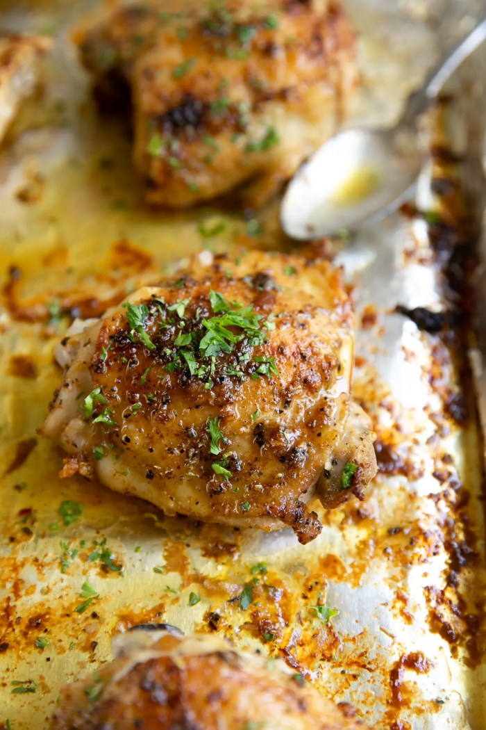 Baked chicken thighs garnished with fresh chopped parsley.