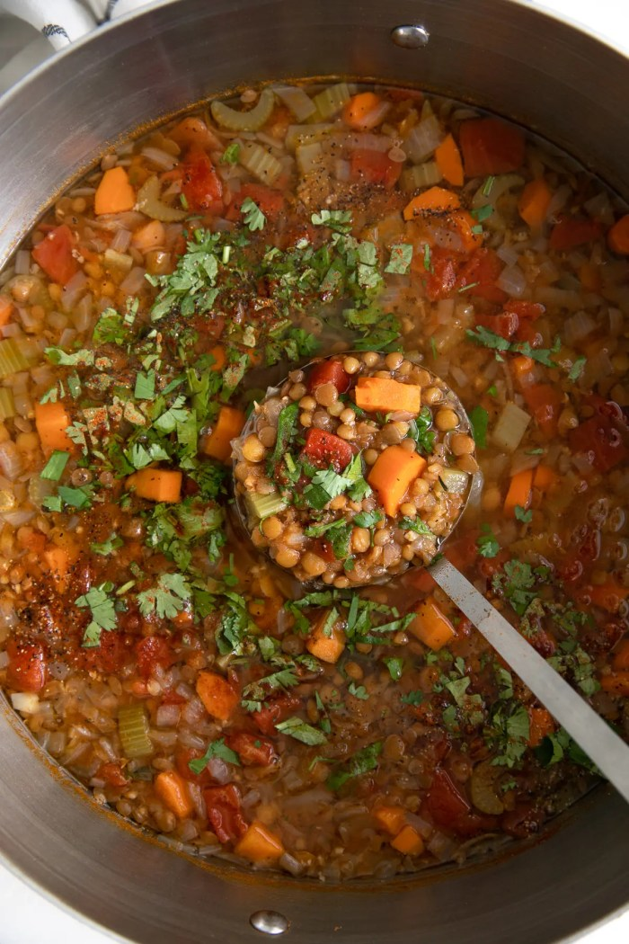Large pot of lentil soup cooked in a rich tomato broth with carrots and fresh chopped parsley..