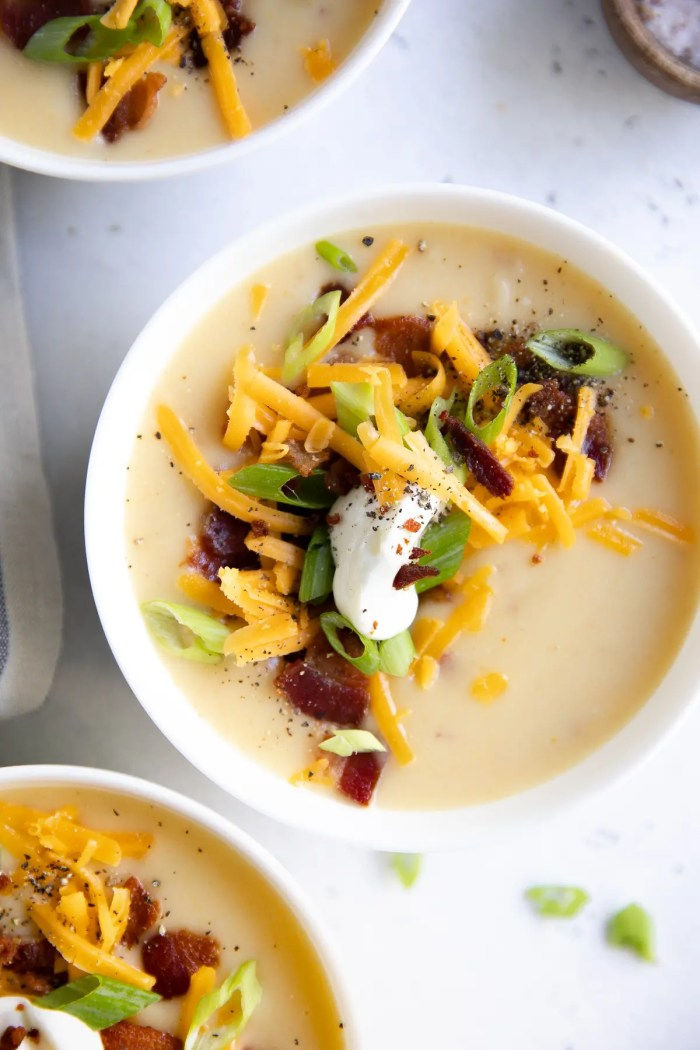 White bowl filled with creamy potato soup and topped with green onions, sour cream, cheddar cheese, and bacon.