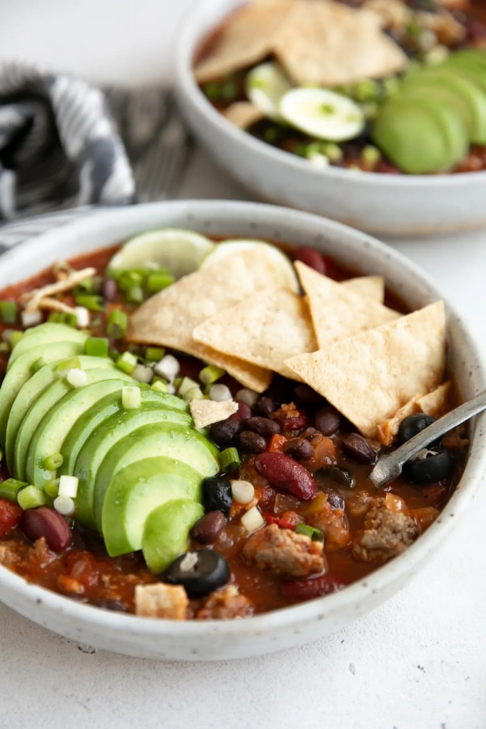 Large white shallow bowl filled with taco soup and garnished with sliced avocado, green onions, sliced lime, and tortilla chips.