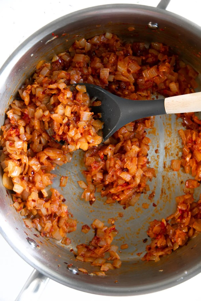 Chopped yellow onion, garlic, crushed red pepper, and tomato paste cooking in a large pan.