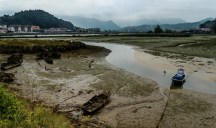 Eb in de riviermonding. Ebb at the mouth of the river with skeleton boat wrecks emerging in the mud!