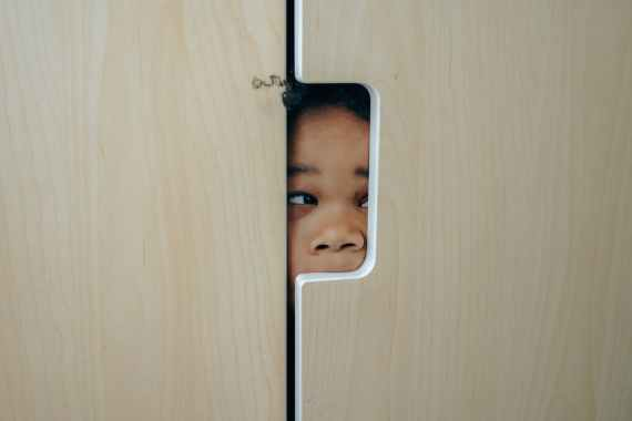 playful black little girl hiding in closet