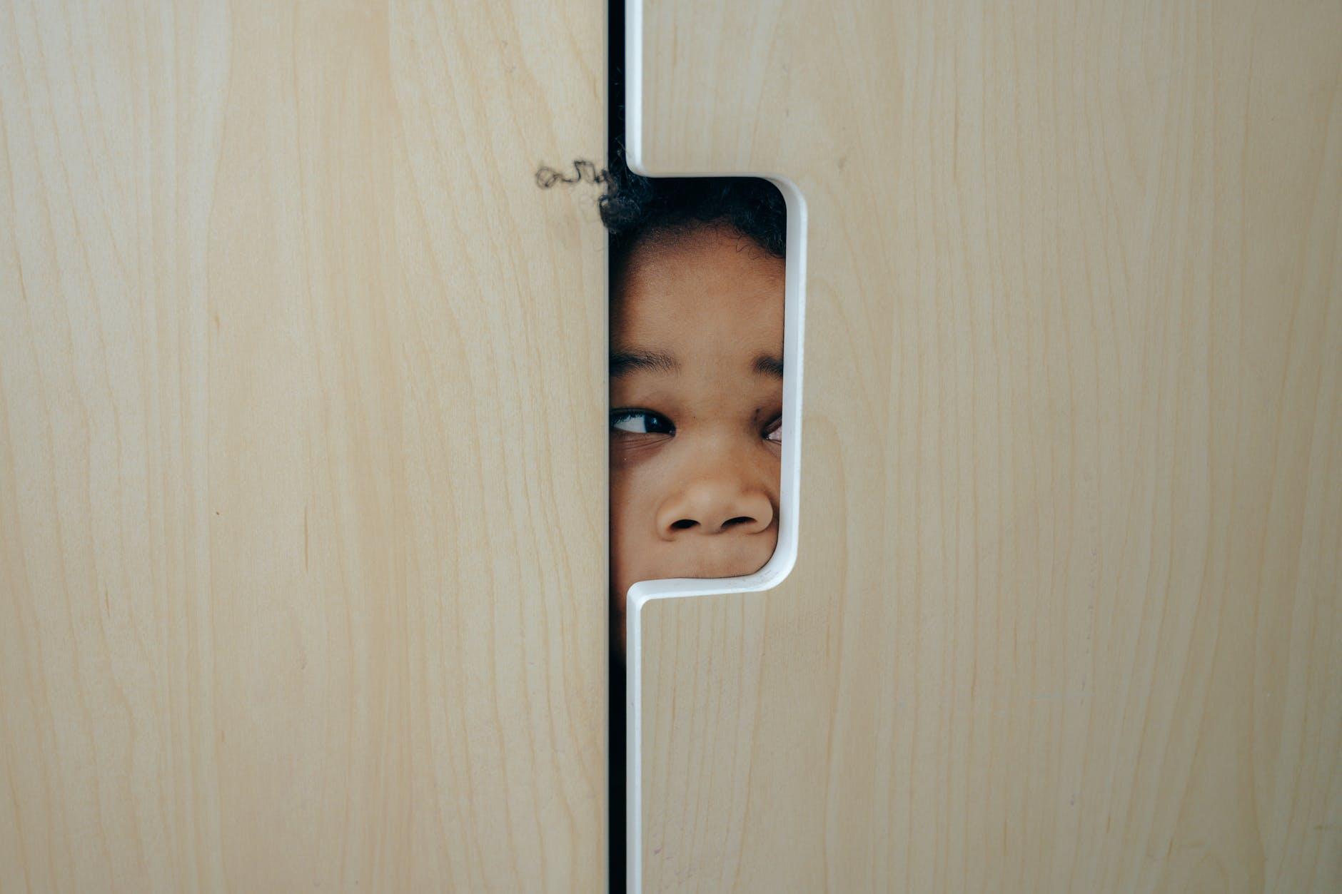 playful black little girl hiding in closet