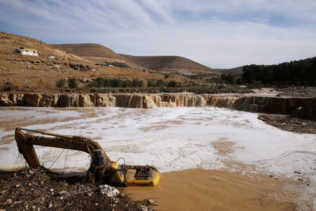 An excavator is partially submerged in a stream as civil defense members look for missing persons after rain storms unleashed flash floods, in Madaba city, near Amman, Jordan, November 10, 2018. REUTERS/Muhammad Hamed