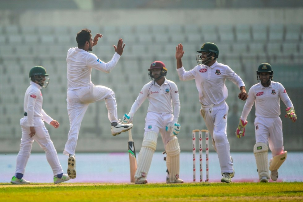 Bangladesh cricketer Mehidy Hasan (2nd L) celebrates with his teammates after the dismissal of the West Indies cricketer Devendra Bishoo (C) during the third day of the second Test cricket match between Bangladesh and West Indies at the Sher-e-Bangla National Cricket Stadium in Dhaka on December 2, 2018. (Photo by MUNIR UZ ZAMAN / AFP)        (Photo credit should read MUNIR UZ ZAMAN/AFP/Getty Images)