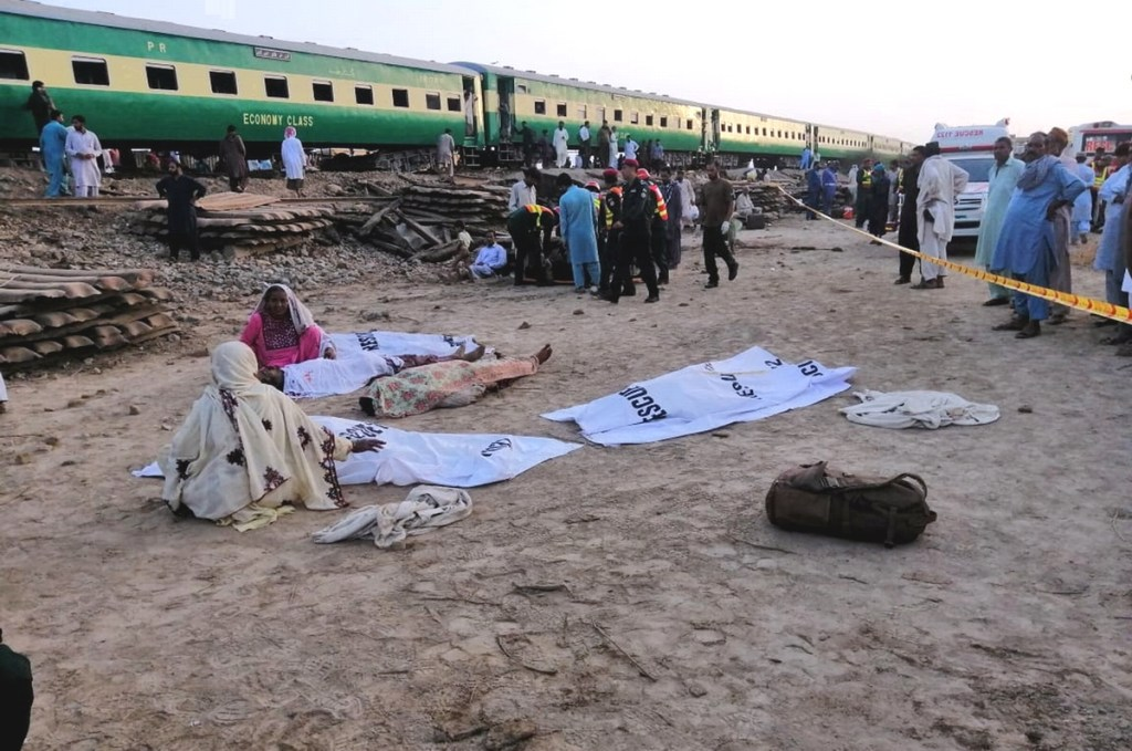 RAHIM YAR KHAN, PAKISTAN, JULY 11: Pakistani women sit besides the bodies of the trains accident at the site after a passenger train crashed into a freight train at Rahim Yar Khan district in southern Punjab province on July 11, 2019.  A passenger train crashed into a stationary freight train in Pakistan on Thursday, killing 11 people and injuring more than 60 under overturned carriages, police said. ( Muhammad Reza - Anadolu Agency )
