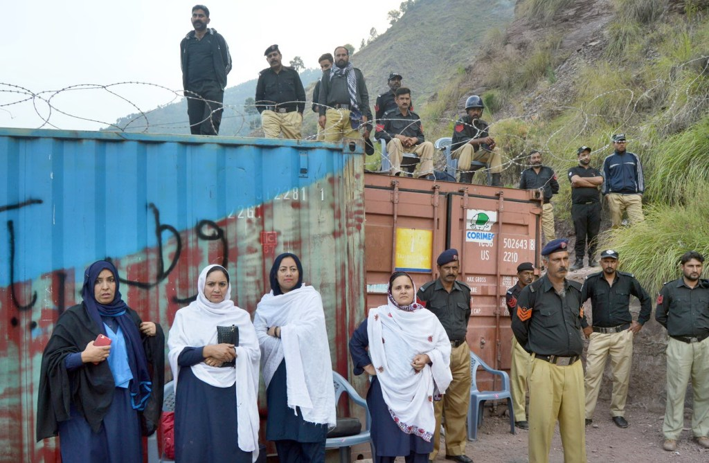 Pic14-022 CHANARI: Oct14- Police personnel stand alert as they sealed Line of Control Road while women police is also present here. ONLINE PHOTO by Shabbir Anjum