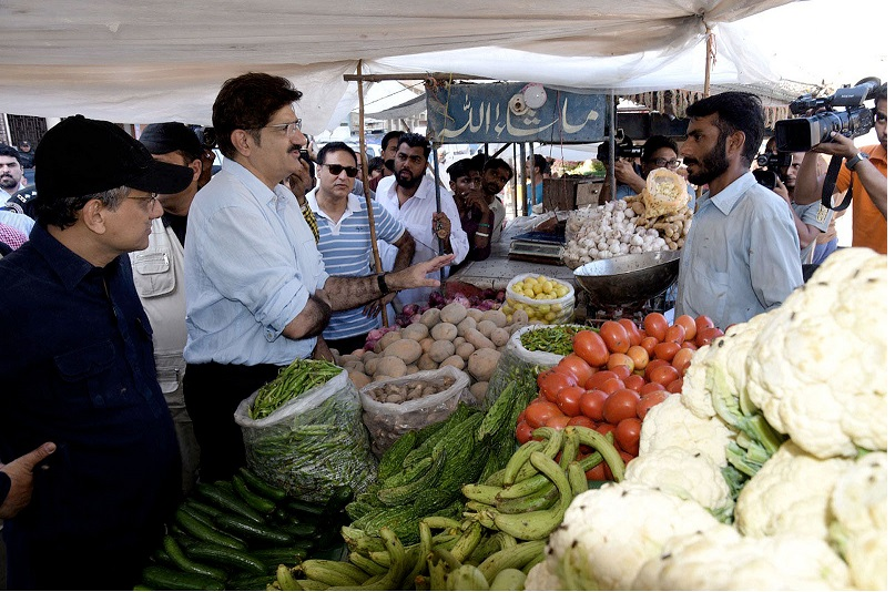 Karachi: Sindh Chief Minister Syed Murad Ali Shah during his visit to Allahwala Society, Korangi urges a vegetable vendor to ensure cleanliness by putting his trash into dustbin constructed across the road.—NNI, October 13, 2019