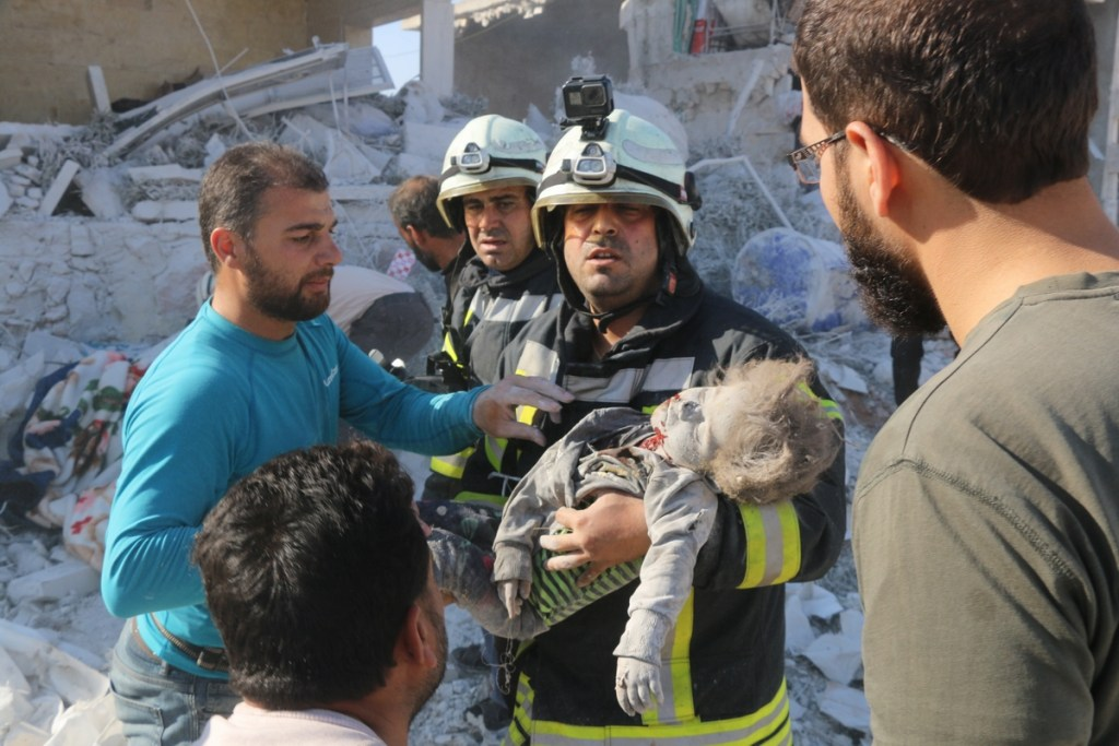 IDLIB, SYRIA - NOVEMBER 06: [EDITORS NOTE: Image depicts death] A firefighter carries the dead body of a child, who was trapped under rubbles, after airstrikes by warplanes of Assad Regime and Russia hit areas within the de-escalation zone, in Al-Sahara town of Syria on November 06, 2019. Airstrikes left at least 8 dead and more than 10 injured.  ( Abdurezzak Sakirdi - Anadolu Agency )