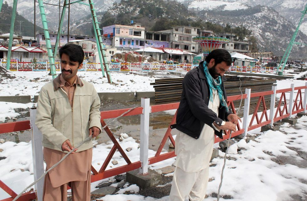 NATHIAGALI: Jan28 - Local men checking broken PESCO Electricity line, after heavy snowfall in the area. ONLINE PHOTO by Sultan Dogar
