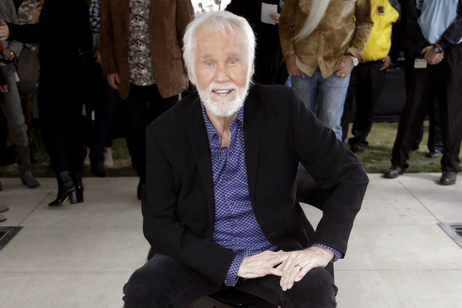 """FILE - In this Oct. 24, 2017 file photo, Kenny Rogers poses with his star on the Music City Walk of Fame in Nashville, Tenn. Actor-singer Kenny Rogers, the smooth, Grammy-winning balladeer who spanned jazz, folk, country and pop with such hits as """"Lucille,"""" """"Lady"""" and """"Islands in the Stream"""" and embraced his persona as """"The Gambler"""" on record and on TV died Friday night, March 20, 2020. He was 81. (AP Photo/Mark Humphrey, File)"""