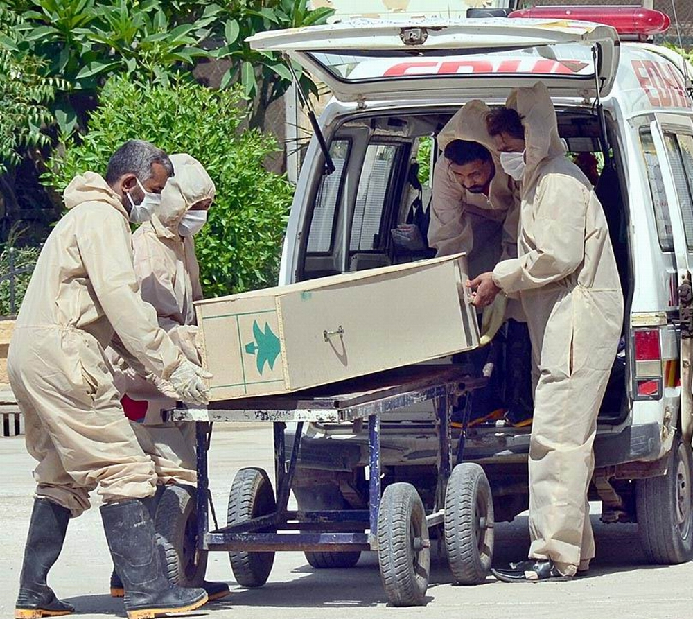 APP36-21 HYDERABAD: May 21 – Edhi Rescue workers shifting coffin of a corona patient dead body in an ambulance from isolation ward of COVID-19 at Civil Hospital. APP photo by Farhan Khan