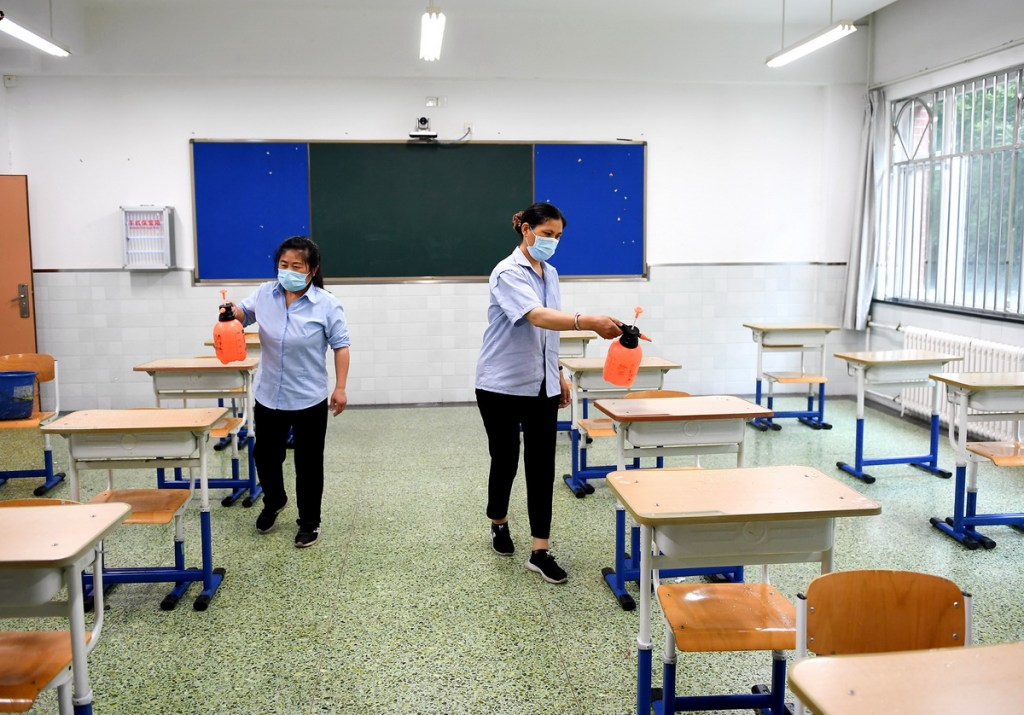 (200703) -- BEIJING, July 3, 2020 (Xinhua) -- Staff members disinfect a classroom at the No. 12 Middle School in Beijing, capital of China, July 3, 2020. This year's national college entrance exam in China will start from July 7. Strict anti-coronavirus measures are required across the country to ensure the safety and health of the candidates for the exam. (Xinhua/Ju Huanzong)