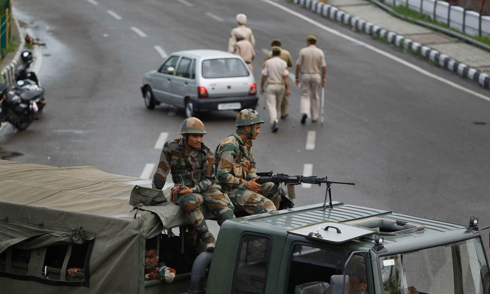 Indian army soldiers guard during restrictions in Jammu, India, Monday, Aug. 5, 2019. India's government issued a revocation of the special constitutional status of its portion of Kashmir on Monday amid an uproar in Parliament and a huge troop deployment in the region. The constitutional provision forbids Indians from outside the region from buying land or permanently settling in the Muslim-majority territory. (AP Photo/Channi Anand)