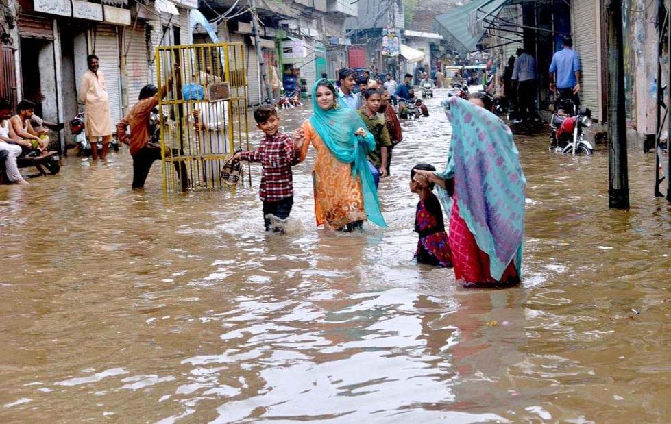 APP44-09 LAHORE: August 09 – Residents passing through the rain water accumulated streets at Baghban Pura due to heavy rain in the provincial capital. AP photo by Rana Imran