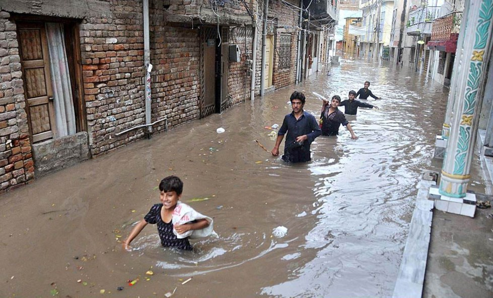 APP43-13 RAWALPINDI: August 13 – Residents passing through the stagnant water at Amarpura's flooded street after early morning's heavy rain. APP photo by Abid Zia